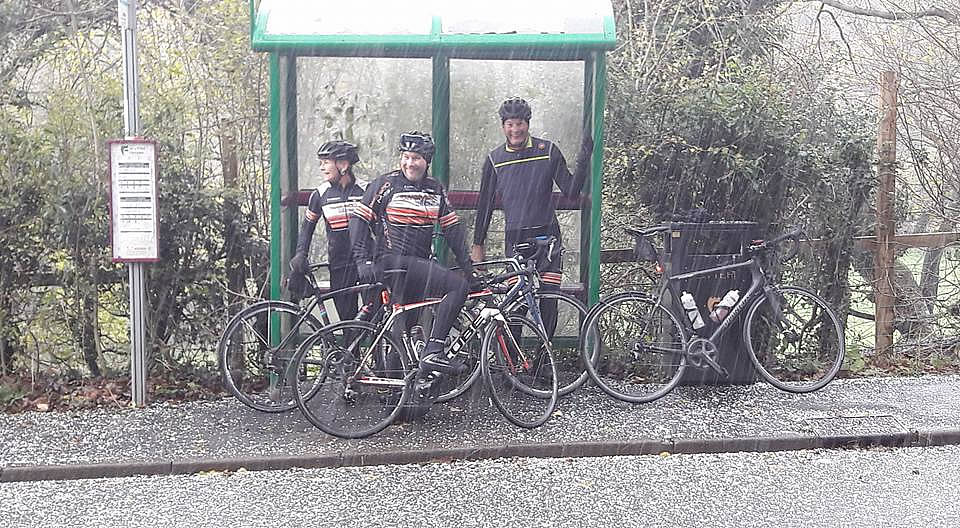 cyclists sheltering bus stop hailstone