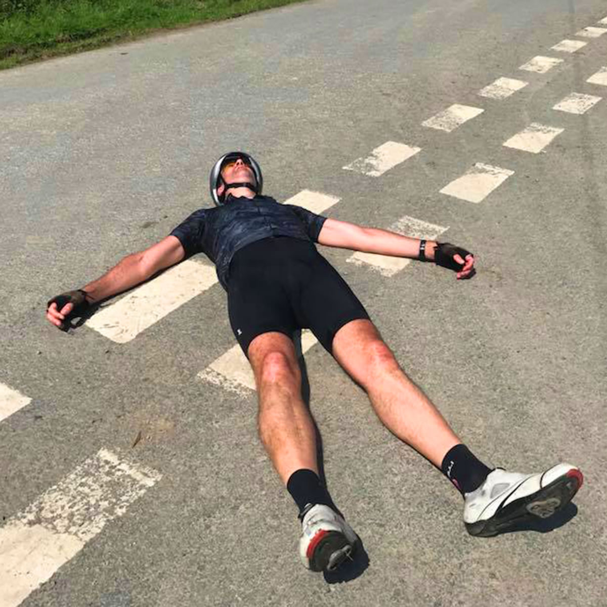 tired cyclist resting on road
